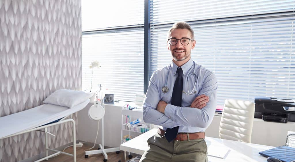 Portrait Of Smiling Mature Male Doctor With Stethoscope Standing By Desk In Office