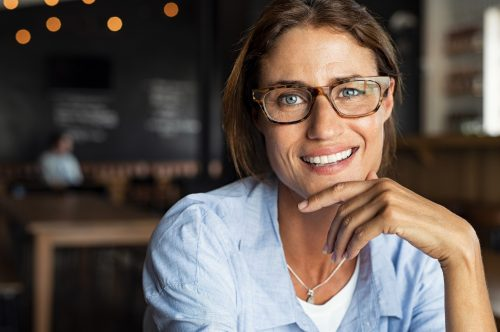 Portrait of happy mature woman wearing eyeglasses and looking at