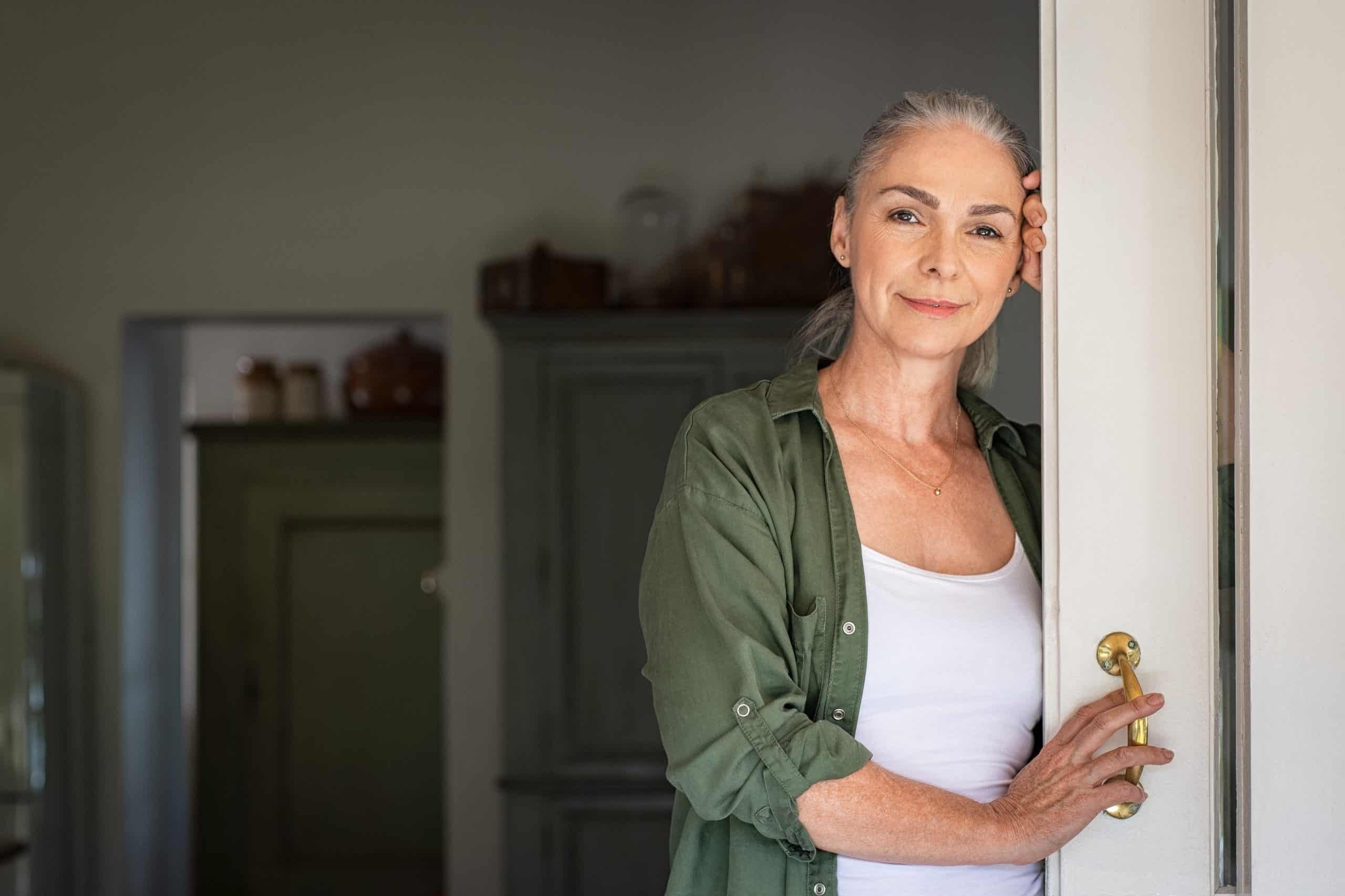 Portrait of senior woman leaning against door at home and lookin