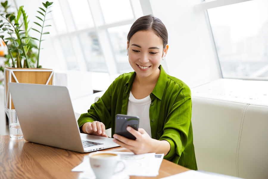 A woman wearing green on laptop computer, holding phone, wearing earbuds.