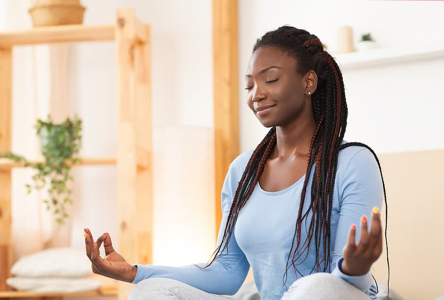 An image of an African American women meditating. Woman with long braids in a blue shirt relaxing with mindfulness app.